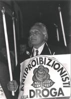 Pannella durante una fiaccolata antiproibizionista con cartello al collo e fiaccola in mano  (BN)