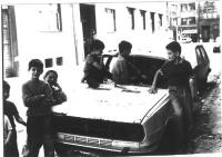 bambini giocano dentro un'auto sforacchiata dai proiettili nelle strade di Sarajevo. (BN)
