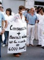 """""""Emma Bonino con mascherina sulla bocca e cartello al collo: """"""""Civitavecchia più Montalto di Castro 40 Km di costa uguale 6.000 megawatt!"""""""""""""""