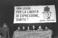 """""""convegno in un teatro. Banner: """"""""una legge per la libertà di espressione subito! Logo PR rosa nel pugno, atipico"""""""". Alla tribuna sta parlando Antonio"""