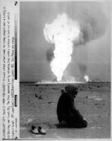kuwaitiano prega nel deserto, sullo sfondo fiamme dell'impianto di raffinazione del petrolio (BN) agenzia