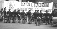"""""""poliziotti in assetto antisommossa in fila davanti ai manifestanti radicali (coperti) che reggono uno striscione (che compare sulla testa dei polizio"""