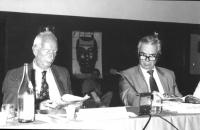 """ritratto di Augusto Premoli (senatore del Partito Liberale) e Leo Solari (a una conferenza radicale). Sullo sfondo, il manifesto radicale: """"Paola Coop"""
