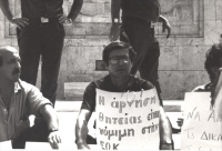 Cicciomessere in un sit con un cartello al collo scritto in greco. (BN)