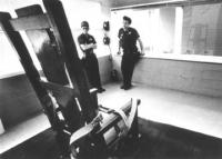 foto di una sedia elettrica all'interno della stanza della morte con due poliziotti. (BN)