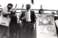 """""""Pannella parla davanti al parlamento europeo durante uma manifestazione antinucleare. Una ragazza accanto a lui tiene un manifesto ecologista scritto"""