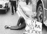 """""""Marcia antimilitarista Trieste - Aviano. Pannella sdraiato sulla strada a P.za della Libertà ad Udine, mentre passa un autobus. Tiene al collo un car"""