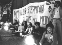"""""""Fiaccolata per sollecitare la approvazione della mozione del Parlamento Europeo contro lo sterminio per fame. Giovani seduti per terra con fiaccole i"""