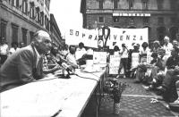 """""""Conferenza stampa di Pannella in Piazza Montecitorio. Striscione: """"""""sopravvivenza '82"""""""", tavolo referendario, molti giornalisti, molti militanti con"""
