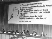 """""""Pannella e Publio Fiori, insieme ad altri seduti sul palco dell'auletta dei gruppi parlamentari a Roma. Dietro il banner dice: """"""""II convegno internaz"""