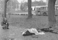 un soldato della guardia nazionale croata, inginocchiato, prega accanto ai corpi di due civili uccisi in un'aiuola al centro della città. (BN) foto ag