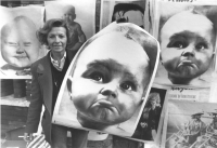 Emma Bonino a Porta Portese tiene in mano un poster con la faccia di un neonato.  (BN). Ottima. Curiosa