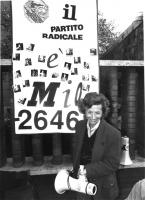 """""""Emma Bonino sorridente a porta portese accanto ad un cartello che dice: """"""""MIO. -2646, logo e scritta PR""""""""   (BN). Ottima"""""""