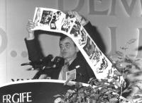 Un bosniaco tiene in mano una serie di foto di Sarajevo distrutta mentre parla dalla tribuna del 36° congresso I sessione. (BN) ottima