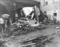 risultati disastrosi di una alluvione, fango e macchine rovesciate. (BN)