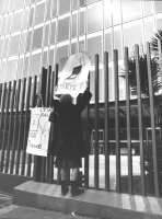 """""""manifestazione davanti alla sede RAI TV di viale Mazzini. Manifestante appende un cartello davanti all'ingresso: """"""""C'è la RAI, attento al portafoglio"""