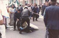 manifestazione radicale in occasione del vertice dei capi di Stato. La polizia trascina via un manifestante con cartello.