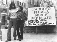 """""""Piazza del Pantheon. Due ragazzi abbracciati passano davanti ad un banner """"""""l'aborto in Italia non è più un reato, discutiamo insieme l'applicazione"""