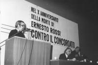"""""""Angiolo Bandinelli parla dalla tribuna del Teatro Adriano, in presidenza Pannella e Mellini. Banner """"""""nel X anniversario della morte di Ernesto Rossi"""