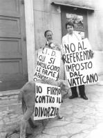 """""""due militanti divorzisti con cartelli al collo: """"""""No al referendum imposto dal Vaticano"""""""", """"""""LID, qui si raccolgono le firme a favore…."""""""", ed una pec"""