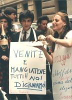 """Negri con cartello al collo: """"Venite e mangiatene tutti. Noi digiuniamo"""", con fette di torta in mano, manifesta con altri militanti contro la censura"""
