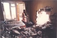 una donna guarda la sua casa in cui è entrata una granata che ha prodotto uno sfacelo. Ottima