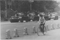 Un ragazzo cinese corre in bicicletta per sfuggire all'accerchiamento dei carri armati mandati dal governo per soffocare nel sangue la protesta di pia