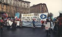"""Marcia di Pasqua '83. Striscioni durante la marcia: """"""""Pasqua 1983 uniti per la vita e la qualità della vita."""""""" """"""""associazione contro lo sterminio per"""