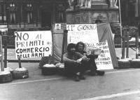 """Due militanti seduti in una piazza con cartelli: """"No ai primati del commercio delle armi"""""""", """"11° giorno di digiuno""""."""