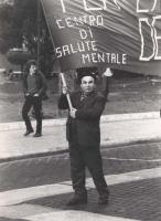 """Manifestazione di protesta contro una legge regionale che riapre i manicomi. Un manifestante innalza lo striscione: """"""""centro di salute mentale"""""""" (BN)"""""""