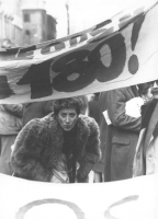 """Manifestazione di protesta contro una legge regionale che riapre i manicomi. Una manifestante sbuca da sotto uno striscione su cui si legge solo : """"""""1"""