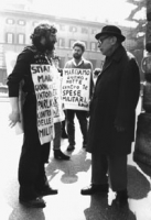 """""""Ivan Novelli, cartello al collo: """"""""marciamo giorno e notte contro le spese militari"""""""" ed un altro militante, parlano con un passante. Walk around del"""
