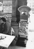 """""""Tavolo con cartelli: """"""""walk around contro l'aumento delle spese militari. (+35%)"""""""", """"""""marciamo giorno e notte contro le spese militari"""""""". """"""""obiezione"""