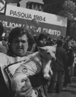 marcia Pasqua '84. Signora abbraccia un cane, sullo sfondo il banner della marcia e palloncini.