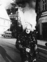 Pannella in divisa croata per la strada, sullo sfondo fumo di un incendio. (BN)