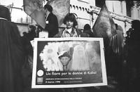 """""""Un fiore per le donne di Kabul"""". Una bambina tiene al collo il poster ufficiale della manifestazione dell'8 marzo contro la politica antidroga dell'O"""