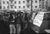 """PROVINI. comizio volante su un camion aperto (mentre piove). Striscione: """"quando la patria chiama: signorno!"""", """"legge civile per gli obiettori, Italia"""