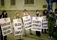 """""""Un fiore per le donne di Kabul"""".  Mosca. Militanti radicali con cartelli al collo in cirillico e in inglese (""""Silence=complicity PR"""", """"No recognition"""