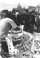 """""""La marcia della pace raggiunge San Pietro, sullo sfondo. Cartelloni del PR ammucchiati per terra: """"""""disarmare per cambiare"""""""" con poliziotti intorno."""