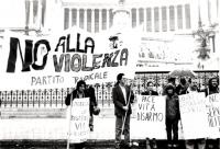 """""""Corteo radicale sotto la pioggia. Rutelli davanti all'altare della patria regge, insieme ad altri, uno striscione: """"""""No alla violenza. PR"""""""". Cartelli"""