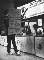 """26° congresso PR. Un contestatore passa con un cartelo davanti alla presidenza. Sul cartello c'è scritto: """"Partito Radicale, alla TV vuoi il massimo a"""