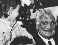 Pannella sorridente (primo piano) guarda una bambina (Altea) che tiene in mano dei fiori. Alla fine del 2° congresso del MCP. (BN)