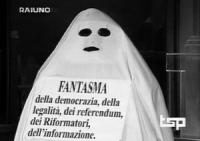 """Prima Tribuna politica per i referendum '97. Pannella si presenta sotto un lenzuolo travestito da fantasma con un cartello: """"fantasma della democrazia"""