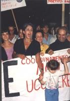 Joan Baez (cantante folk statunitense) alla fiaccolata contro la pena di morte e per la vita di Paula Cooper dietro uno striscione. Canta tenendo per