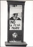 """Emma Bonino sorridente dietro una ghigliottina, durante una manifestazione, tiene al collo un cartello con su scrito: """"no alla pena di morte"""""""