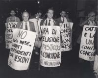 """Strik Lievers e Corleone (in primo piano) insieme ad altri, partecipano a una manifestazione contro il Concordato. Fra i cartelli: """"No agli insegnanti"""