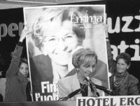 """Emma Bonino, nel corso dell'assemblea dei Mille, sul podio. Dietro di lei, due donne militanti, sollevano il manifesto del comitato """"Emma for presiden"""