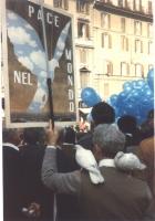 Manifestazione antimilitarista e per l'obiezione di coscienza. Un manifestante, con due colombe sulle spalle, regge un cartellone raffigurante la colo