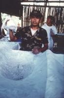 soldato boliviano solleva un sacchetto di coca davanti ad un mare di polvere di cocaina in una raffineria clandestina.