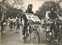 """Manifestazione antinucleare in bicicletta. Un partecipante porta al collo un cartello su cui si legge: """"Sole vento acqua"""". (Vedi foto 1367)"""